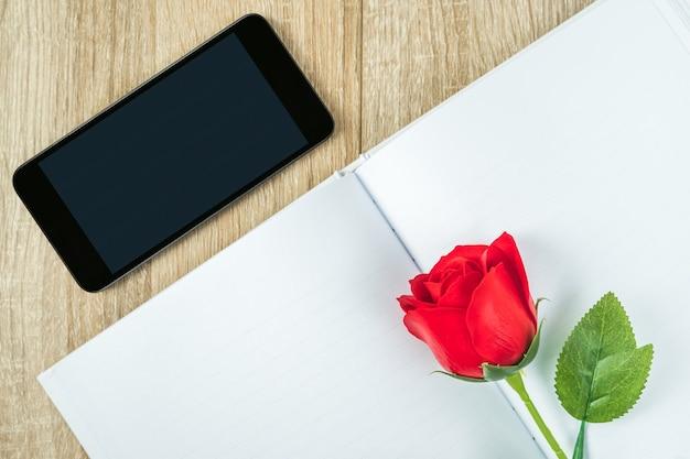 Bovenaanzicht shot van rode rozen op lege notebook dagboek en smartphone op houten tafel, valentine concept