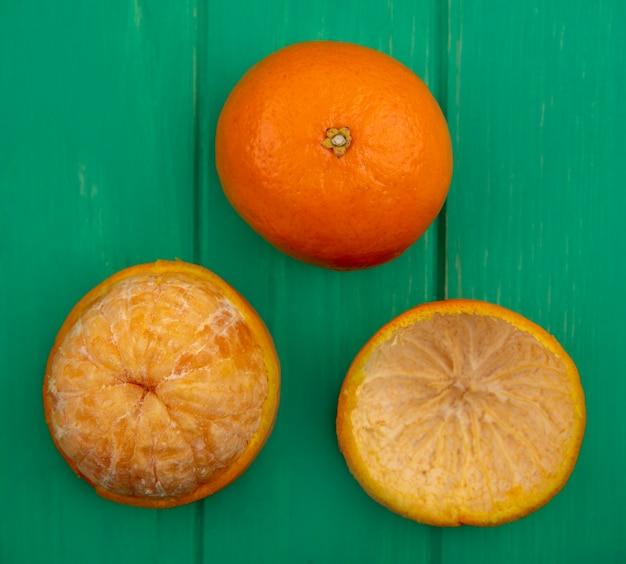 Bovenaanzicht sinaasappel met gepelde schil op groene achtergrond