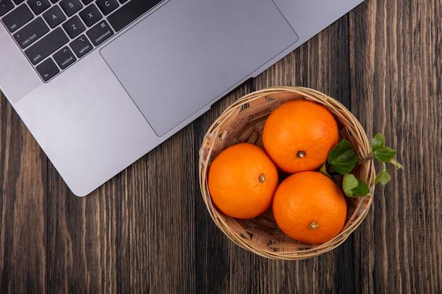 Bovenaanzicht sinaasappelen in een mand met een laptop op een houten achtergrond