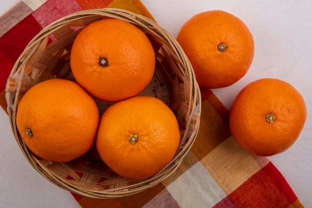 Bovenaanzicht sinaasappelen in een mand op een geruite handdoek op een witte achtergrond