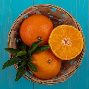 Bovenaanzicht sinaasappelen in een mand op een turkooizen achtergrond