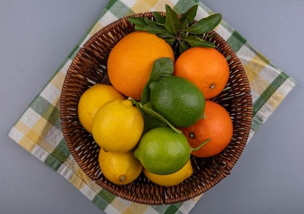 Bovenaanzicht sinaasappelen met citroenen en limoenen (lemmetjes) in een mand op een gele geruite handdoek op een grijze achtergrond