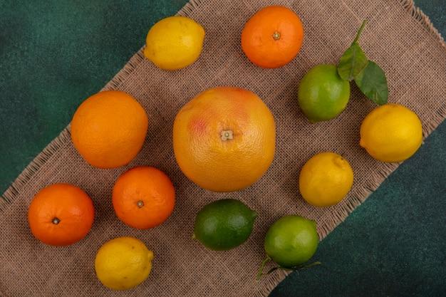 Bovenaanzicht sinaasappelen met grapefruit, citroenen en limoenen (lemmetjes) op een beige servet