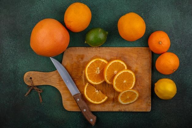 Bovenaanzicht sinaasappelen op snijplank met mes citroen limoen en grapefruit op groene achtergrond