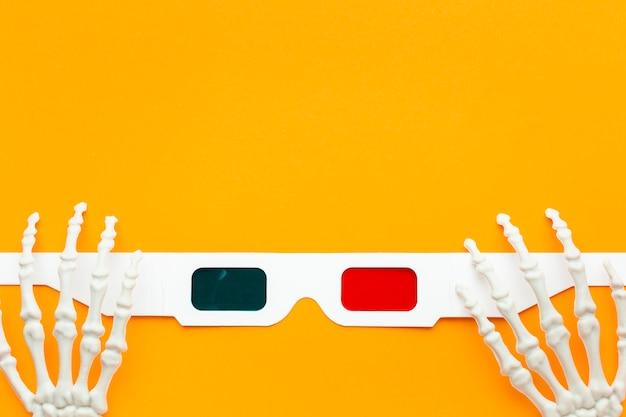 Bovenaanzicht skelet handen en 3d-bril met kopie ruimte