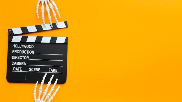 Bovenaanzicht skelet handen en filmklapper met kopie ruimte