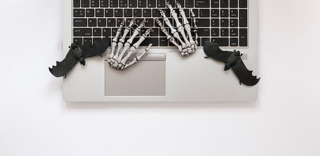 Bovenaanzicht skelet handen op laptop met vleermuizen