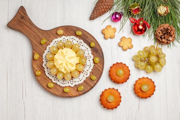 Bovenaanzicht slagroomtaart met kleine zoete taarten en druiven op wit bureau fruitkoekjeskoekjeskoekjestaart