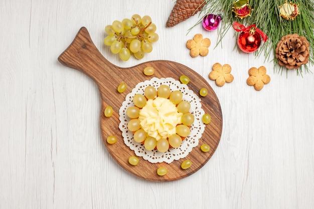 Bovenaanzicht slagroomtaart met verse druiven op wit bureau fruitkoekje cake biscuit pie