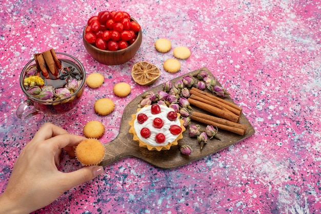Bovenaanzicht slagroomtaart met verse rode veenbessen samen met kaneelkoekjes en thee op de glanzende tafelsuikerzoet