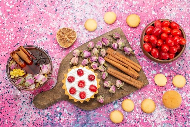 Bovenaanzicht slagroomtaart met verse rode veenbessen samen met kaneelkoekjes en thee op het heldere suikerzoete oppervlak