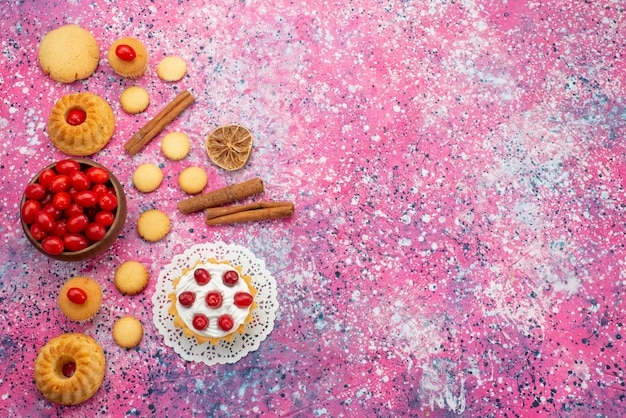 Bovenaanzicht slagroomtaart met verse rode veenbessen samen met kaneelkoekjes op het paarse suikergoed van het bureaukoekje