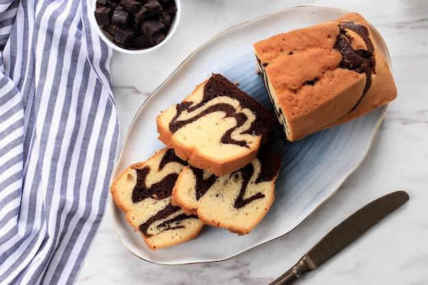 Bovenaanzicht slice marble cake boven keramische plaat op witte marmeren achtergrond. chocolade- en vanillecake