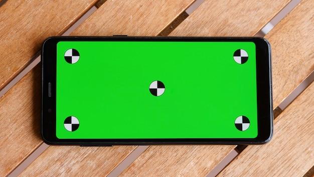 Bovenaanzicht slimme telefoon plaats op tafel hout met groen scherm, close-up de mobiele telefoon is op het bruine bureaublad met chroma key en markeringen.