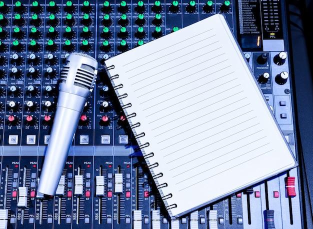 Bovenaanzicht sliver retro vintage microfoon en notebook op console soundboard mixer