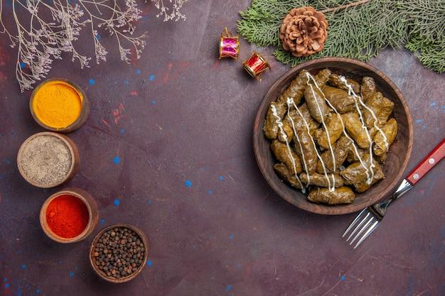 Bovenaanzicht smakelijk blad dolma gehaktschotel met kruiden op donker