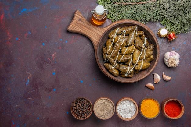 Bovenaanzicht smakelijk blad dolma vleesgerecht met kruiden in het donker
