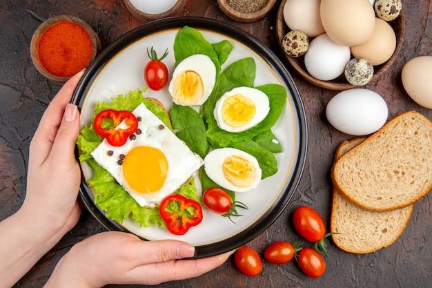 Bovenaanzicht smakelijk broodje met eieren, kruiden en tomaten op donkere tafel
