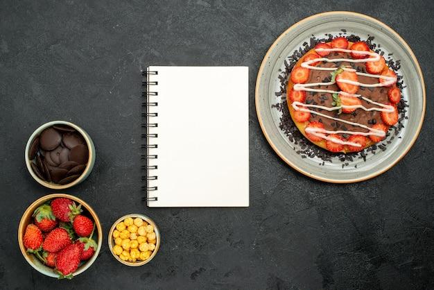 Bovenaanzicht smakelijk cake wit notitieboekje tussen cake met stukjes chocolade en aardbei en kommen chocolade aardbei en hazelnoot op zwarte tafel