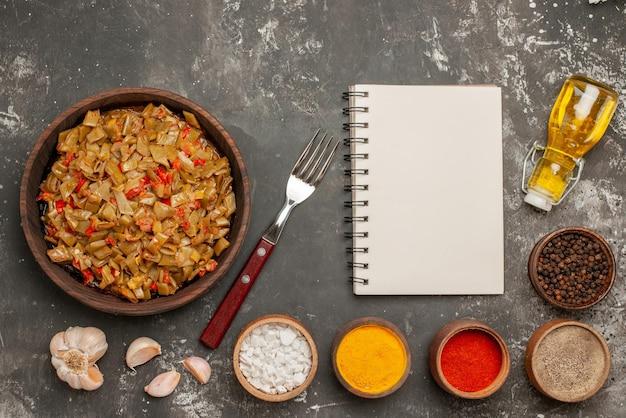Bovenaanzicht smakelijk gerecht de smakelijke sperziebonen met tomaten naast de witte notebook kommen van vijf soorten kruiden knoflook vork fles olie op de donkere tafel