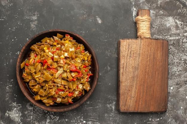 Bovenaanzicht smakelijk gerecht een smakelijk gerecht van sperziebonen en tomaten naast de houten snijplank op de donkere tafel