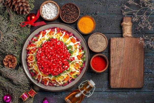 Bovenaanzicht smakelijk gerecht kerstgerecht met zaden van granaatappel naast de snijplank boomtakken met kegels, kruiden en olie