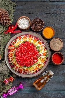 Bovenaanzicht smakelijk gerecht smakelijk kerstgerecht met granaatappel naast de boomtakken met kegels, kruiden en olie