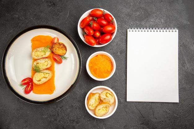 Bovenaanzicht smakelijke aardappeltaarten met pompoen en verse tomaten op de grijze achtergrond diner oven bak kleur schotel slice