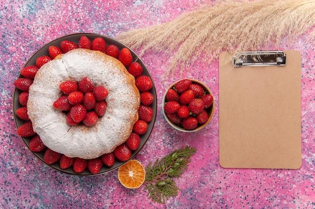 Bovenaanzicht smakelijke aardbeientaart met suikerpoeder op lichtroze