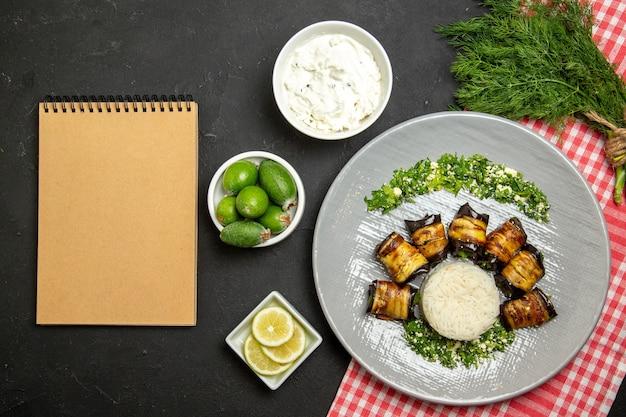 Bovenaanzicht smakelijke aubergine rolt gekookte maaltijd met rijst op zwart