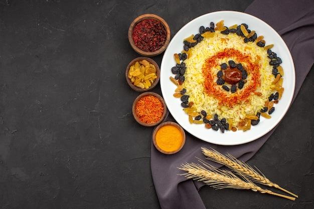Bovenaanzicht smakelijke beroemde oosterse maaltijd bestaat uit gekookte rijst en rozijnen op donker