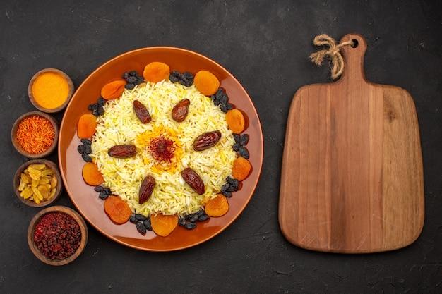 Bovenaanzicht smakelijke beroemde oosterse maaltijd bestaat uit gekookte rijst en verschillende rozijnen op een donker bureau