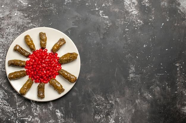 Bovenaanzicht smakelijke blad dolma met gepelde granaatappels op donkere vloer
