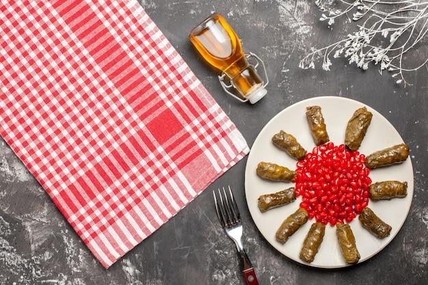 Bovenaanzicht smakelijke blad dolma met granaatappels op donkere vloer