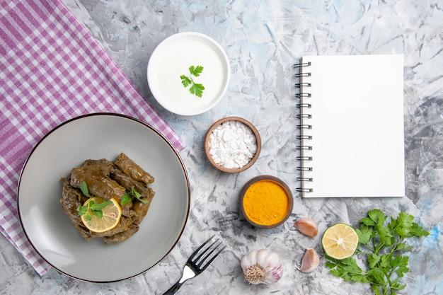 Bovenaanzicht smakelijke blad dolma met kruiden op wit bureau