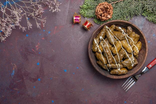 Bovenaanzicht smakelijke blad dolma vleesgerecht binnen bruine plaat op donker