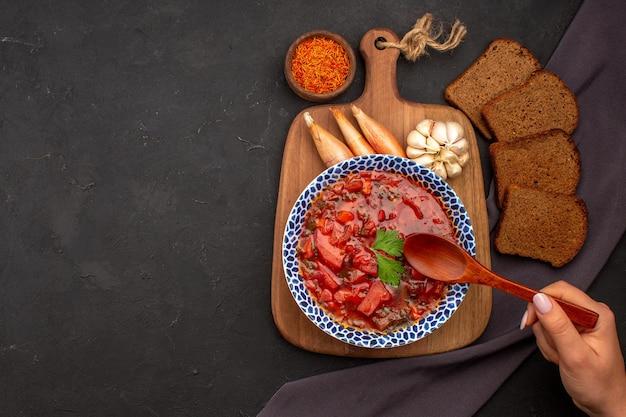 Bovenaanzicht smakelijke borsch oekraïense bietensoep met donkere broden op de donkere ruimte