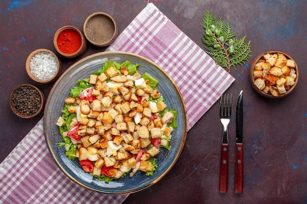 Bovenaanzicht smakelijke caesar salade met beschuit en kruiderijen op het donkere bureau