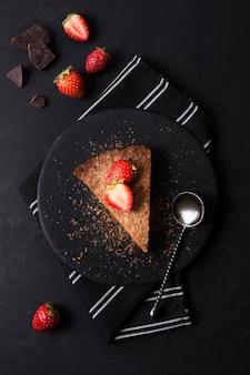 Bovenaanzicht smakelijke cake met aardbei op een bord