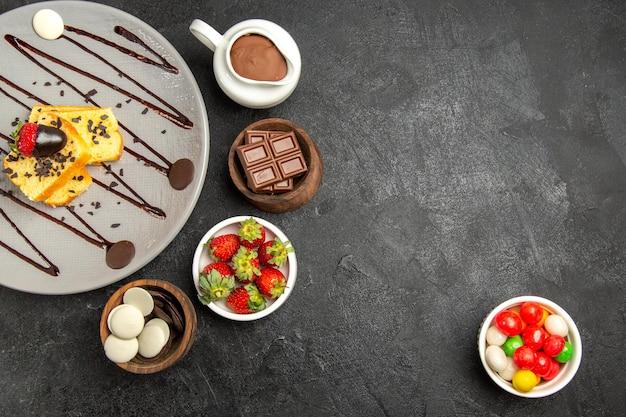 Bovenaanzicht smakelijke cake smakelijke cake met chocolade en aardbeien naast de kommen met chocolade en aardbeien aan de linkerkant en snoep aan de rechterkant van de tafel