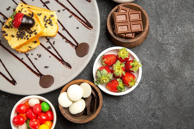Bovenaanzicht smakelijke cake smakelijke cake met chocolade en aardbeien naast de vier kommen met snoep en bessen