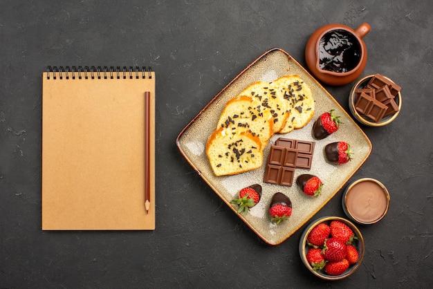 Bovenaanzicht smakelijke cakecake met aardbeien en chocolade tussen kommen chocoladeroomaardbeien en chocolade naast het bruine potlood en roomnotitieboekje
