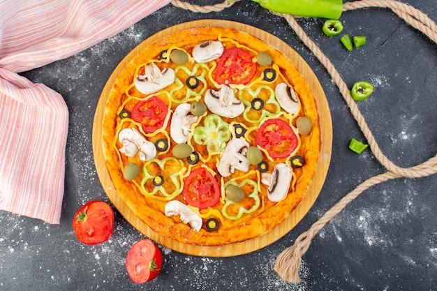 Bovenaanzicht smakelijke champignonpizza met rode tomaten olijven champignons met verse tomaten helemaal over het grijze bureau pizzadeeg italiaans