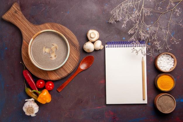 Bovenaanzicht smakelijke champignonsoep met verschillende kruiden op de donkere achtergrond soep champignons kruiden voedsel