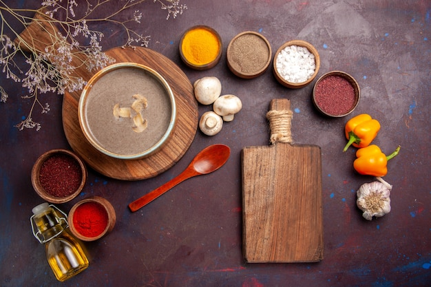 Bovenaanzicht smakelijke champignonsoep met verschillende kruiden op de donkere achtergrond soep, champignons, kruiderijen voedsel maaltijd