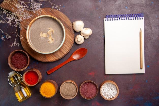 Bovenaanzicht smakelijke champignonsoep met verschillende kruiden op de donkere achtergrond soep paddenstoel kruiden voedsel maaltijd