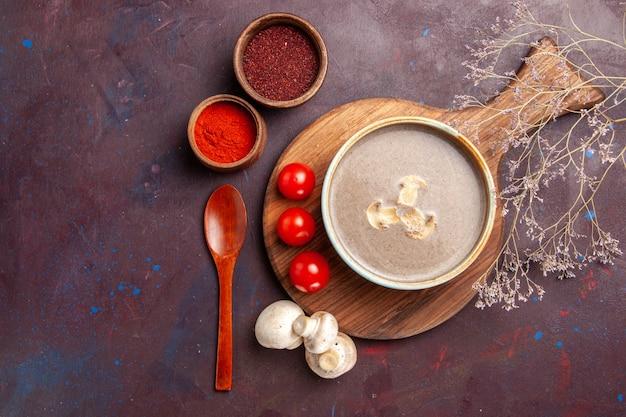 Bovenaanzicht smakelijke champignonsoep met verschillende kruiden op donkere achtergrond soep maaltijd champignons kruiden voedsel