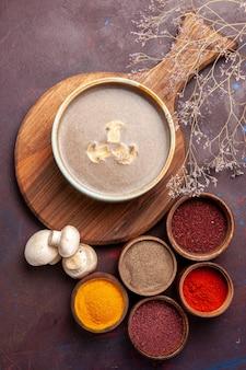 Bovenaanzicht smakelijke champignonsoep met verschillende kruiden op donkere achtergrond soep maaltijd paddestoel kruiden voedsel