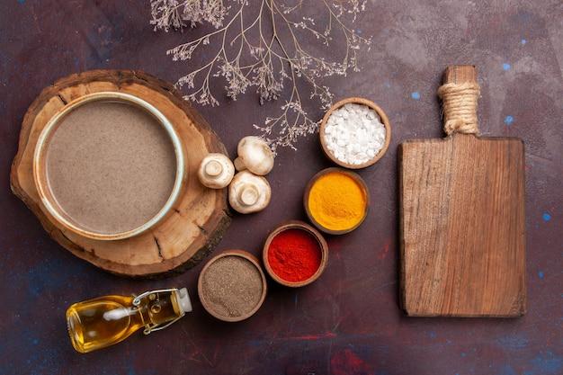 Bovenaanzicht smakelijke champignonsoep met verschillende kruiden op donkerpaarse achtergrond soep kruiden voedsel maaltijd