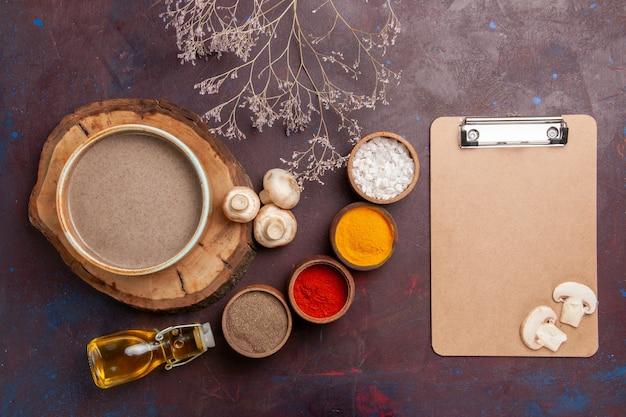 Bovenaanzicht smakelijke champignonsoep met verschillende kruiden op donkerpaarse achtergrond soepkruiden voedsel